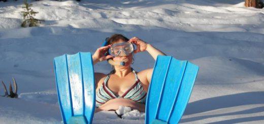 Женщина в купальнике, ластах и акваланге на снегу